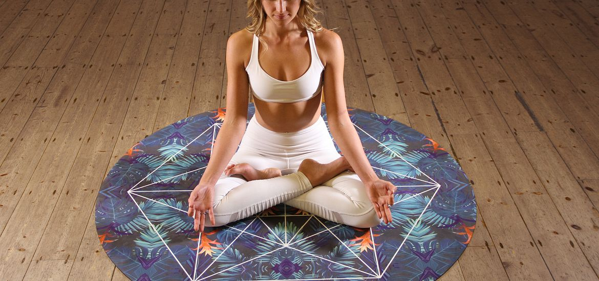Woman sitting on the floor on top of a yoga rug practicing meditation.