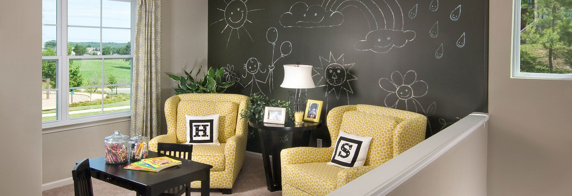 Loft with chalkboard accent wall and 2 chairs and table