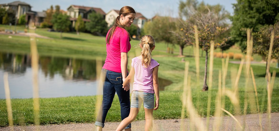Mother and daughter walking around lake