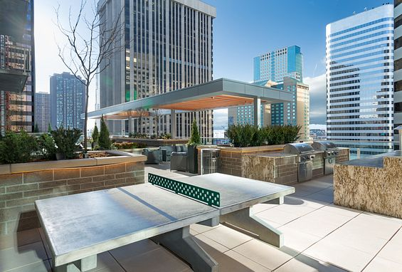 Amenity deck with fire pit, BBQs and ping pong tables the quincy downtown denver apartments