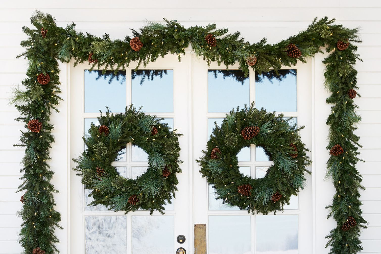 decorated greenery wreaths and garlands on a white front door