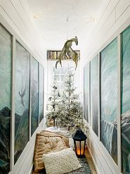 a pair of sparse Christmas trees in a reading nook