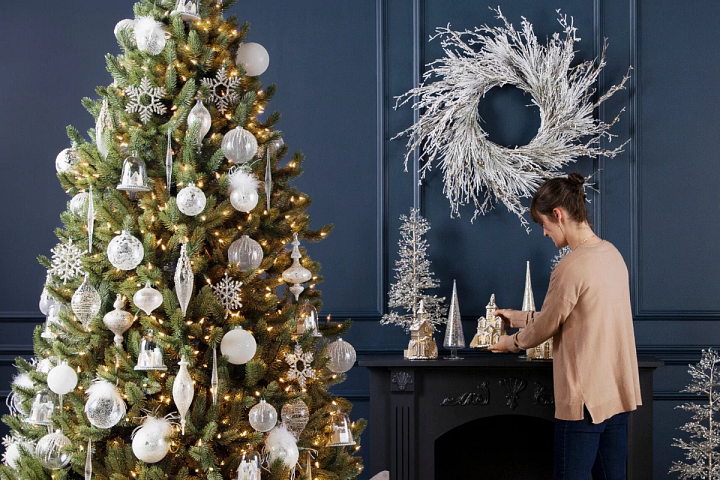 Woman fixing white and gold themed Christmas decorations in a blue room