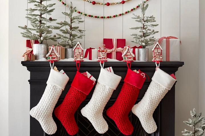 red and white Christmas stockings, decorative stocking holders, gifts, and miniature trees on a black mantel