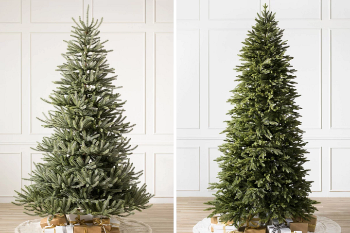 two unlit artificial Christmas trees in a white room