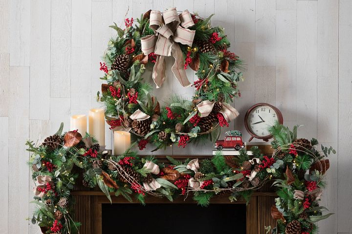 artificial wreath and garland with festive Christmas decorations on a mantel