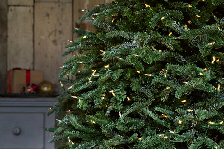 close-up of realistic artificial Christmas tree with clear LED lights