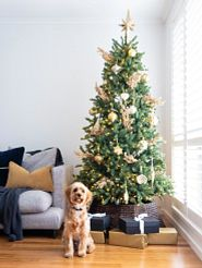 decorated artificial Christmas tree with a puppy in front of it