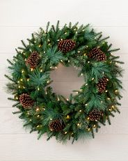 decorated greenery wreath with clear LED lights and pinecones