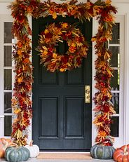 fall-themed greenery wreath and garland on a front door