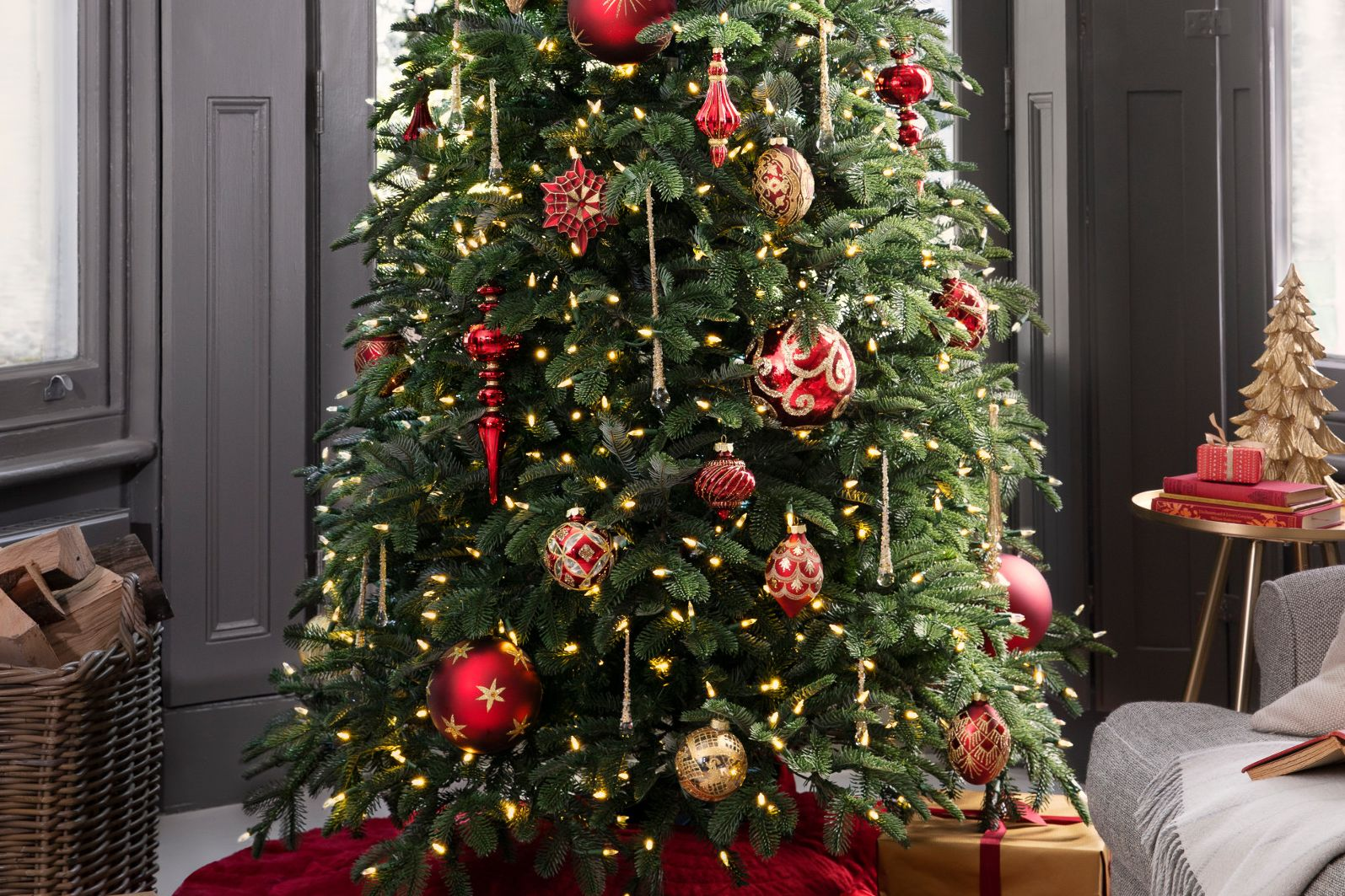 realistic artificial Christmas tree with lights and red and gold decorations