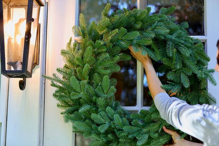 woman hanging an artificial wreath on a glass door