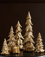 A set of five metallic glitter tabletop trees in varying sizes