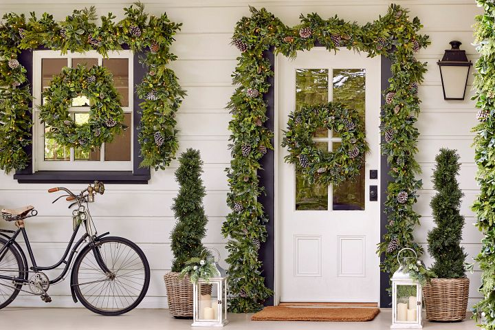 White front porch with various artificial greenery wreaths, garlands, and topiaries