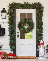 a Christmas-themed wreath and garland on a white front door