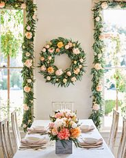 an artificial floral wreath and garland pair in a dining room