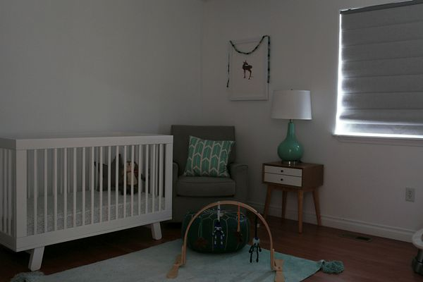 A dark nursery with blackout Bali Roman Shades