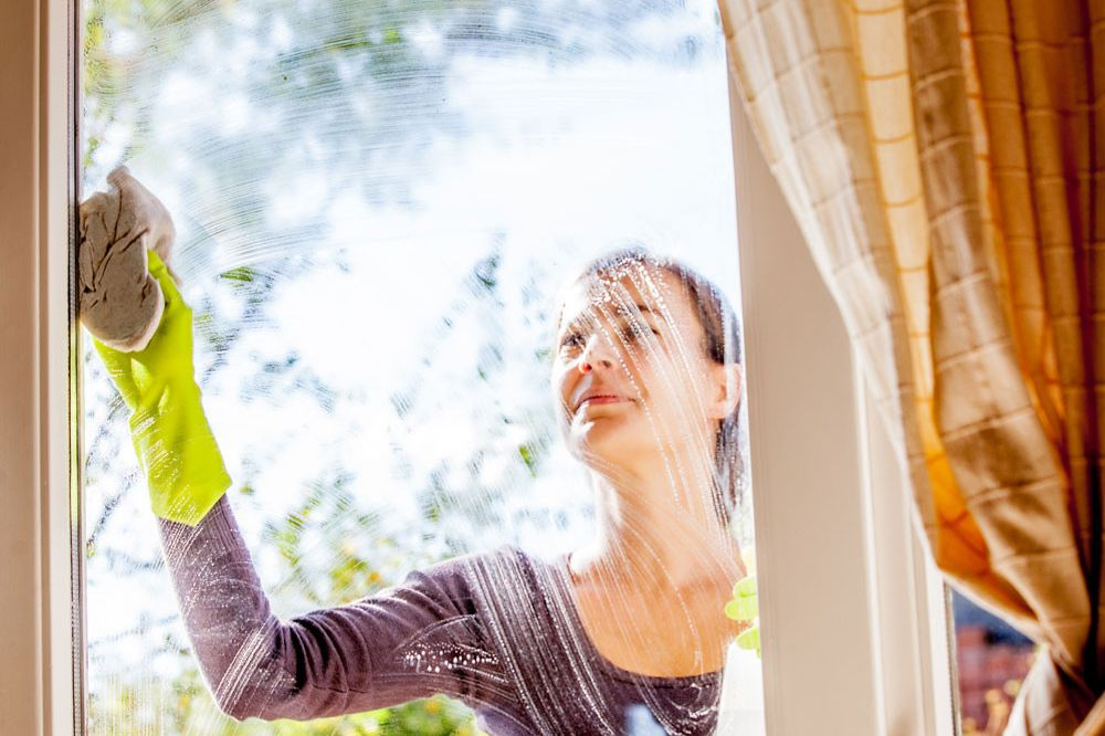 A woman cleans her windows