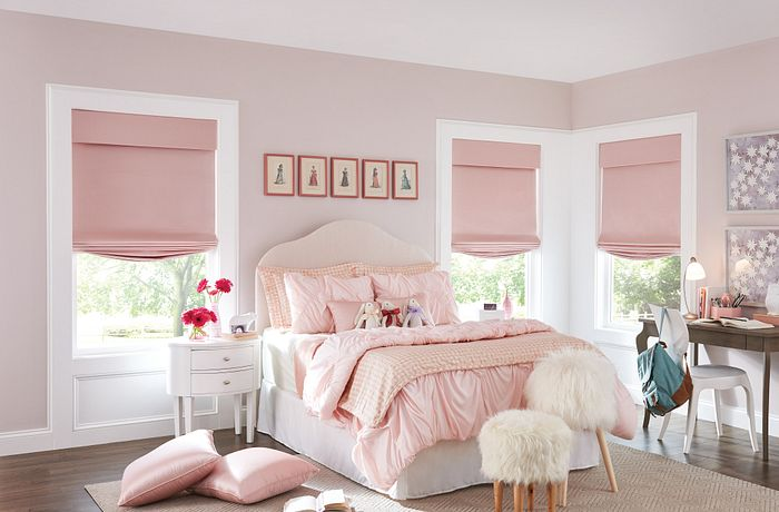 A bedroom with Bali Tailored Roman Shades