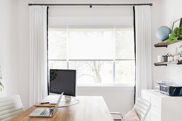 A home office space with Bali motorized shades and drapery