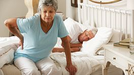 Elderly woman sitting on the edge of her bed grasping her lower back while man is sleeping