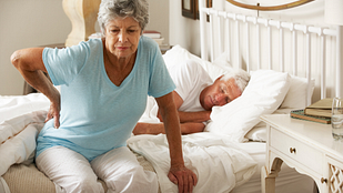 older woman with hip pain in bed