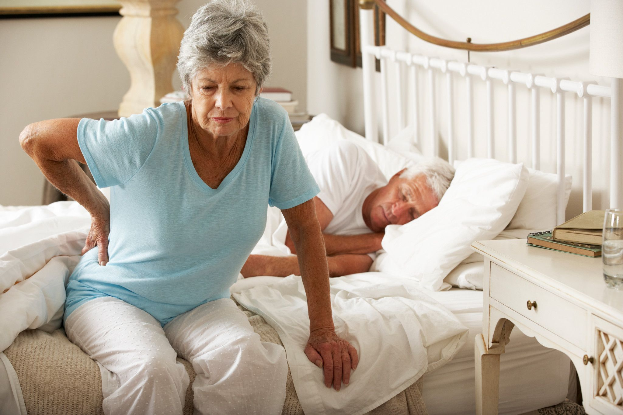 Senior woman getting out of bed with a backache
