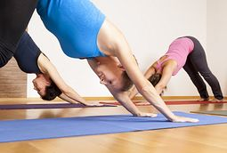 three women doing downward facing dog yoga pose