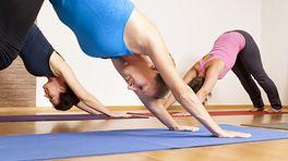 Three women doing downward facing dog yoga pose