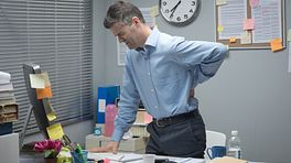 Man standing at his desk, grabbing his lower back in pain