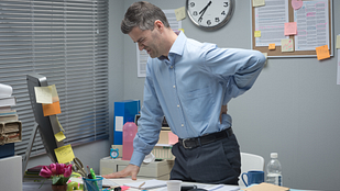 Image of man standing at his desk with lower back pain