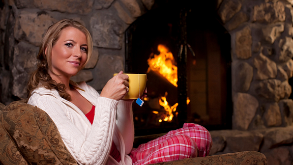 Image of woman drinking tea in front of the fireplace