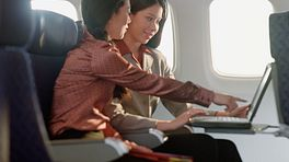 Two women talking while sitting in an airplane