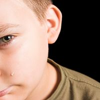 Young boy shown with a tear on his check.