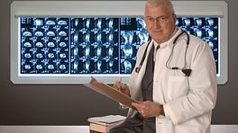 Doctor standing in front of a board of CT scans.