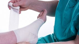 Nurse taping a patient's foot.