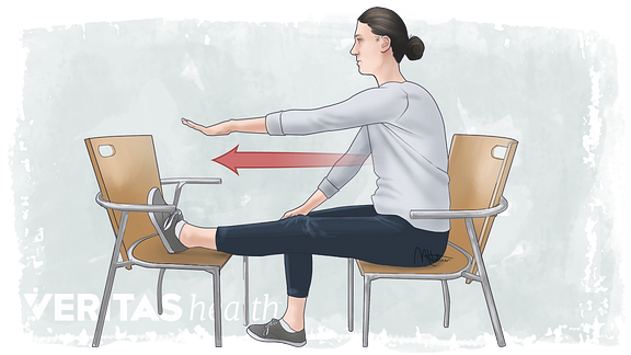 Woman sitting in a chair leaning forward doing a hamstring stretch.