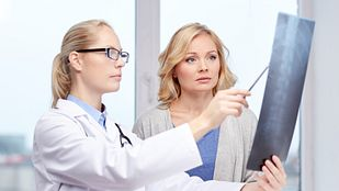 Doctor and patient having a discussion in an office while looking at scans.