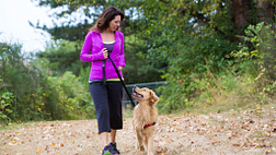 Image of a woman walking her dog on a trail