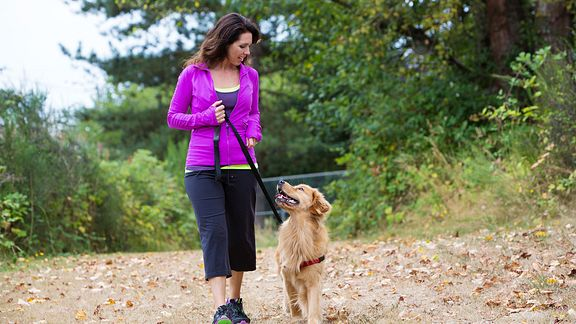 Woman walking her dog on a trail