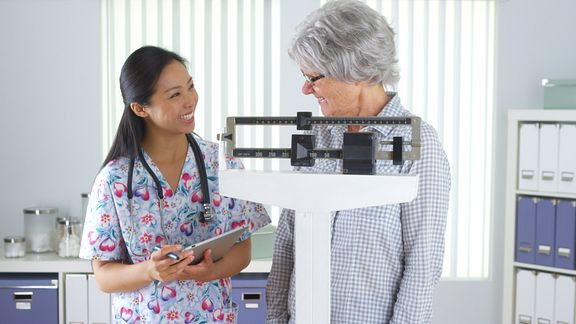 Nurse checking patient's weight