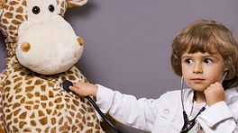 Child dressed up as a doctor examining his stuffed giraffe.