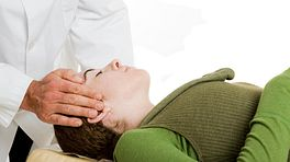 Chiropractor adjusting a supine patient's spine.