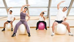 Group performing aerobics with exercise balls.