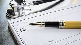 Table with stethoscope, pen, and prescription paper