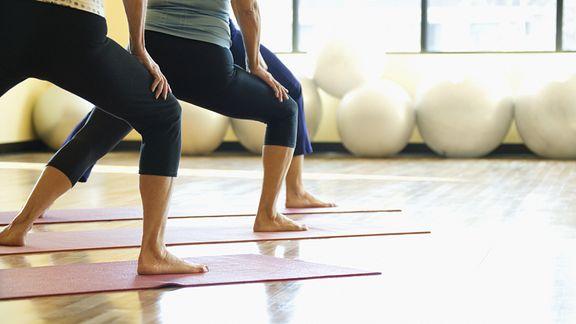 Women on mats in a yoga class