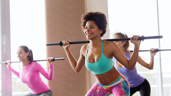 Image of three women performing weighted squats in an exercise class
