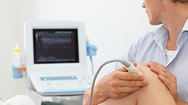 Technician administering an ultrasound on a patient's knee.