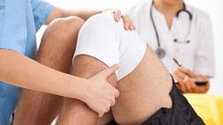 Physical therapist stretching a patients knee.