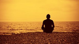 Man meditating on a beach at sunrise.